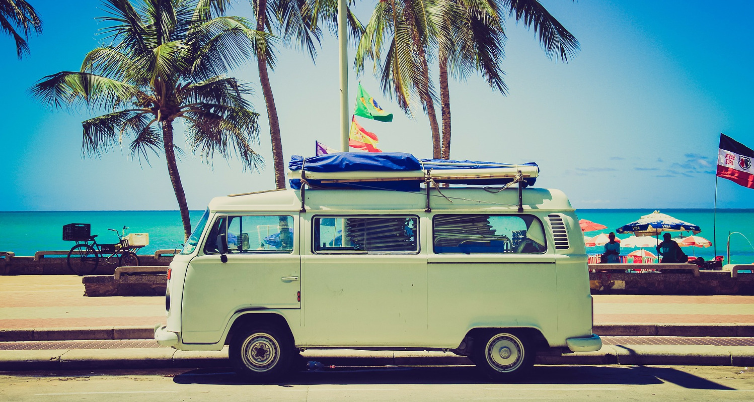 Vintage VW campervan with palm trees and sea