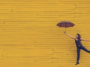 woman holding umbrella jumping against a yellow wooden backdrop