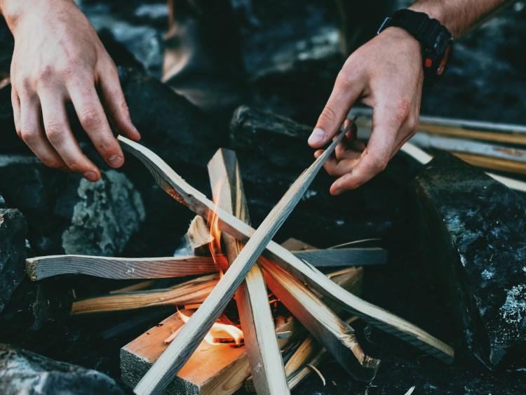 Hände richten Holz am Lagerfeuer aus